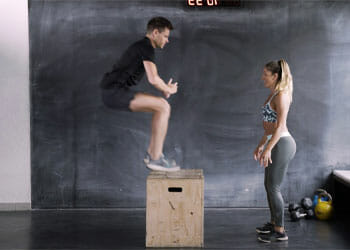 man working out while a woman watches