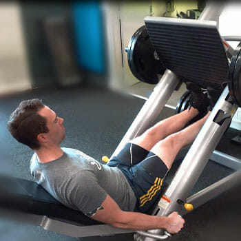 man working out his legs using a leg press machine