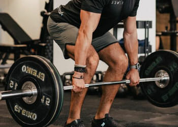 man lifting a long bar dumbbell