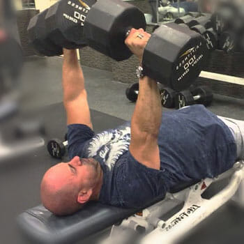 man laying down doing dumbbell press