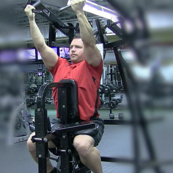 man in a red shirt working out with a machine