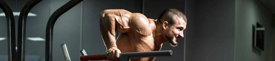 shirtless buff man doing tricep dips inside a gym