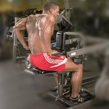shirtless man using a dip machine in a gym