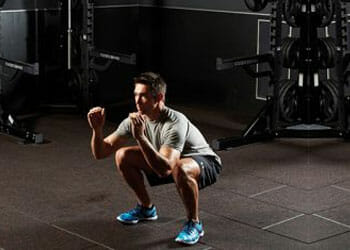 man in a gym about to do a squat jump