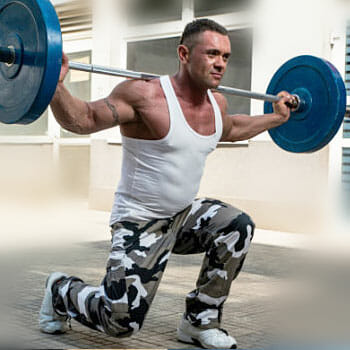 man in a walking lunge position while carrying a barbell