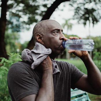 black man wiping his sweat while chugging water