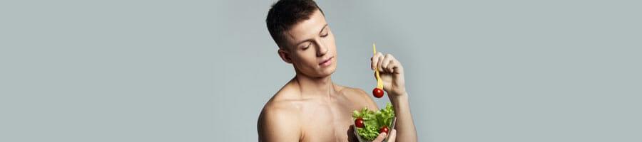 shirtless man devouring a bowl of salad