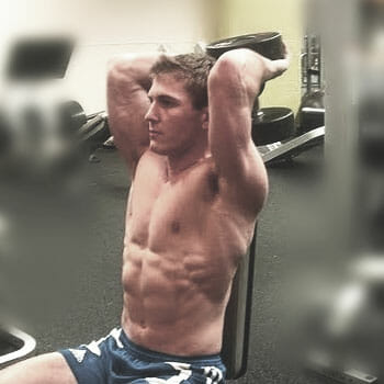 man doing overhead tricep extensions with dumbbells