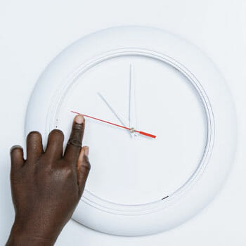 white clock and a hand pointing at it