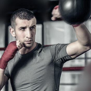 tall man using a speed bag inside a gym