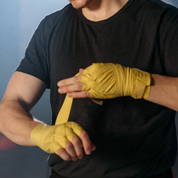 close up image of a man wrapping his hands for boxing