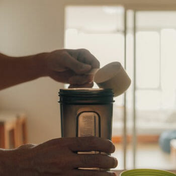 close up image of a man pouring protein powder into a water jug