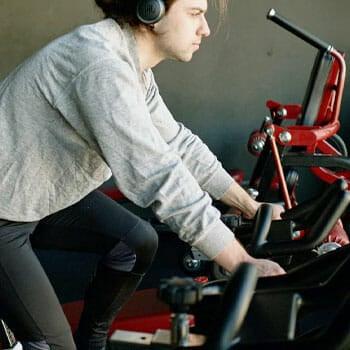 man wearing a grey sweatshirt using a bike inside a gym