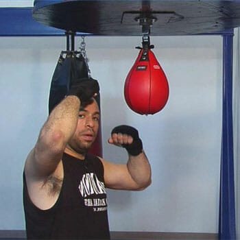 man using a speed bag with boxing gloves