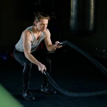 man using ropes inside a gym