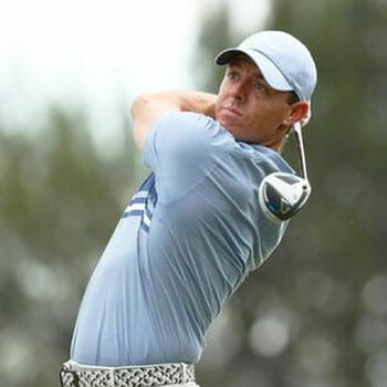 rory mcilroy playing golf with a blue shirt on
