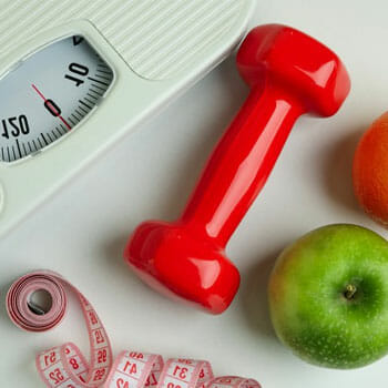 white weighing scale, red dumbbells, apples and tape measure on the floor
