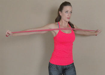 woman wearing a pink top using a resistance band