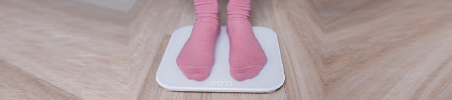 woman with pink socks stepping on a weighing scale