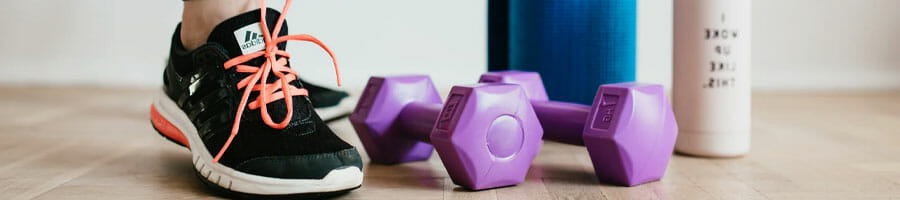 woman's rubber shoes, purple dumbbells, water jug and yoga mat on the floor