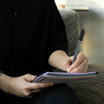close up image of a person using a ballpen on a notebook