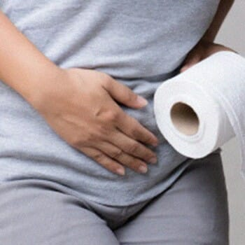 A woman holding a tissue roll and her stomach