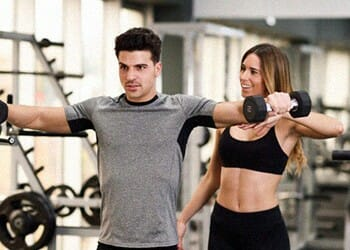 woman teaching a man how to use dumbbells