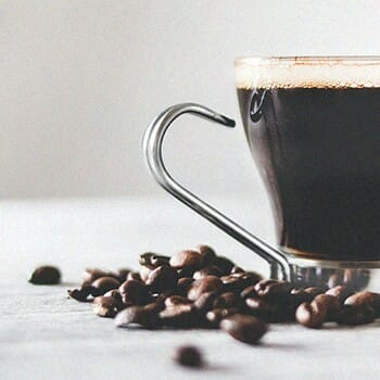 A glass mug of coffee with coffee beans surrounding it