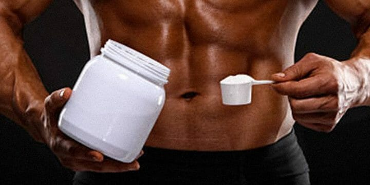 A guy holding a creatine container and a scoop of it