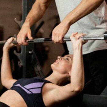 A personal trainer 'Spotting' to help the person lifting the weights