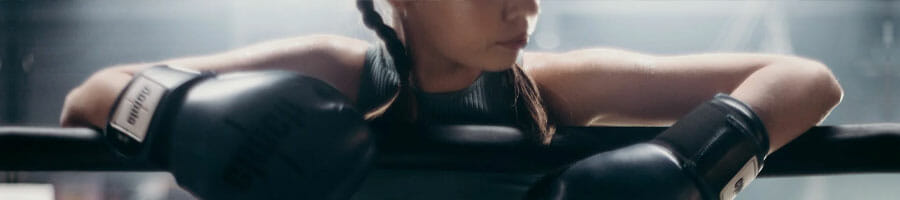 woman wearing a boxing gloves inside a gym