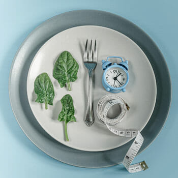 fork, leaves, small blue clock, measuring tape placed on a plate