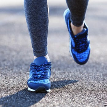 close up image of a person's blue rubber shoes while walking