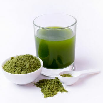 still shot of a green juice, powder and spoon
