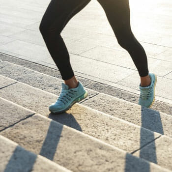 lower leg view of a woman jogging up the stairs