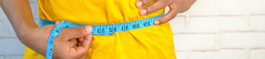 man using a measuring tape on his waist