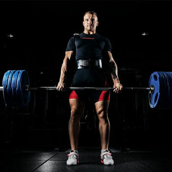 bodybuilder practicing barbell shrugs in a gym