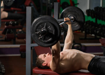 man using a barbell laying down on a bench