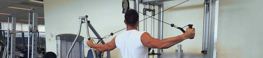 man working out using the cable machine