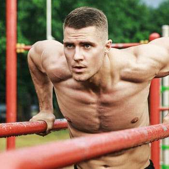 shirtless man doing chest dips in a park