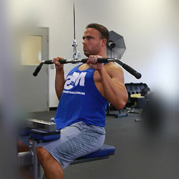 man using a cable machine in a gym