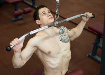 shirtless man in a wide grip lat pulldown position