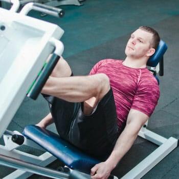 man using a leg press machine inside a gym