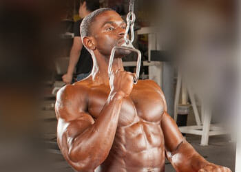 shirtless buff man pulling a lat machine with one arm