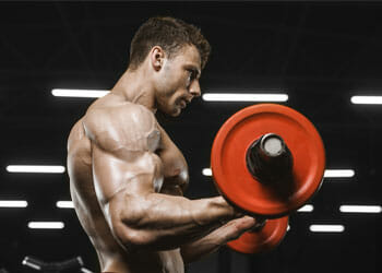 shirtless man using a heavy barbell inside a gym