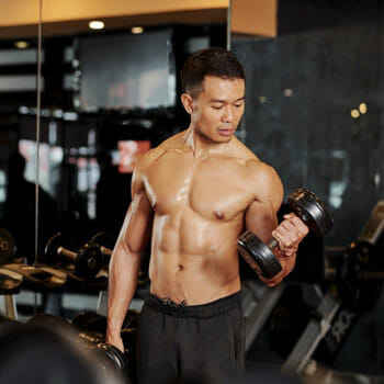 shirtless asian man working out with a dumbbell on one arm