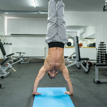 shirtless man in a hand stand position inside a gym