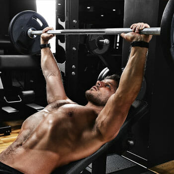 shirtless man doing bench press