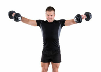 man in gym clothes raising dumbbells on both hands