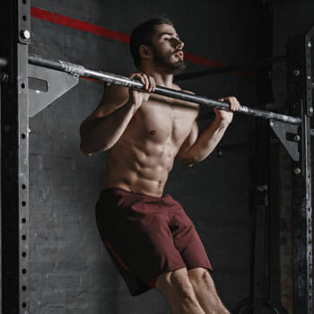 shirtless man in a pull up position